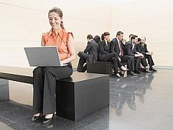 Businesswoman using laptop away from co-workers
