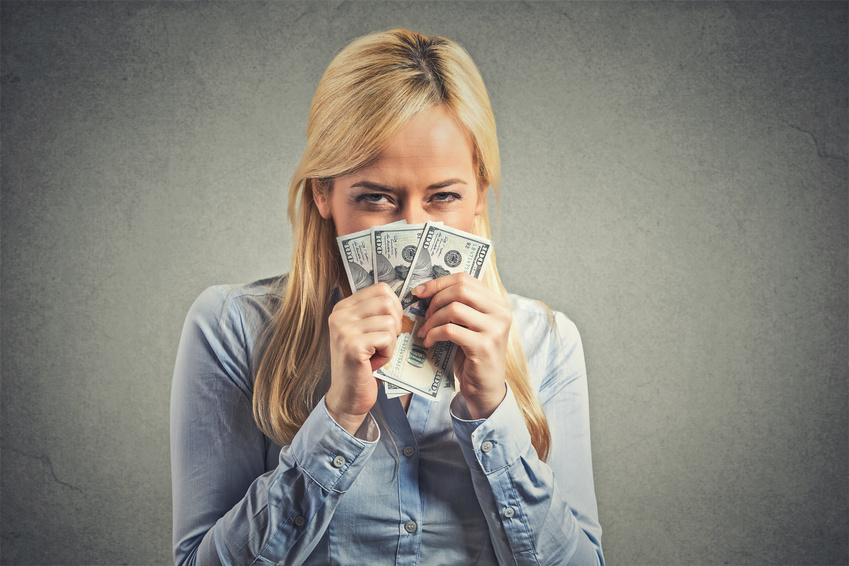 Closeup portrait greedy young corporate employee, woman, holding dollar banknotes tight isolated on gray wall background. Negative human emotion facial expression. Financial gain concept