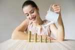 Woman pours coins on the table smiling