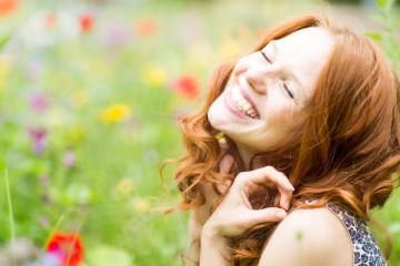 schne lachende Frau in der Blumenwiese