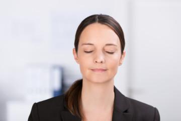frau entspannt im büro mit geschlossenen augen