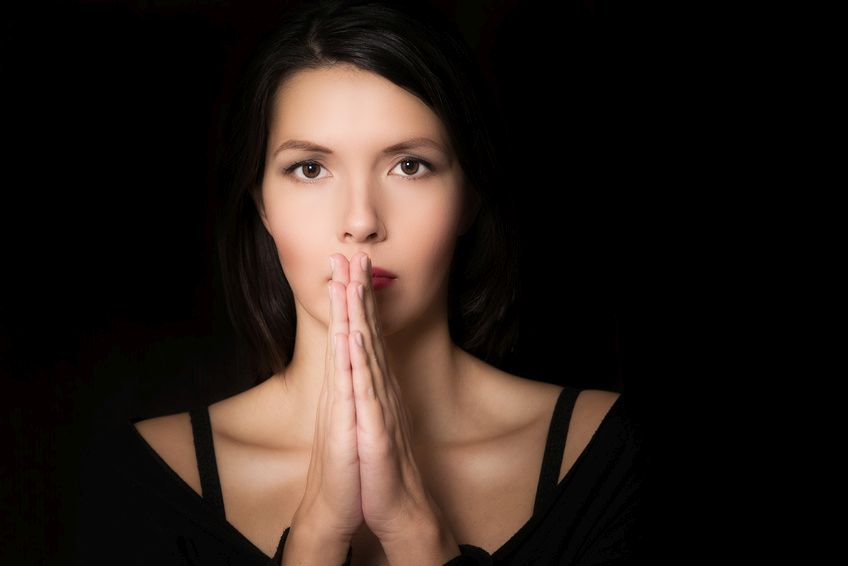 Dark evocative portrait of a spiritual young woman praying with her hands clasped and an intent look in her eyes