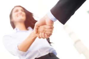 Business woman with face out of focus shakes hands with business man who can see only the hand.